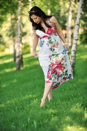 beautiful  woman walking on  grass in  birch grove .  summers day. photo