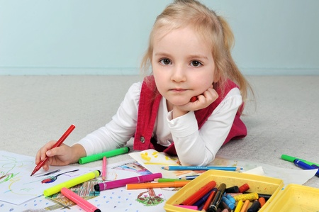Beautiful little girl is drawing  on paper photo