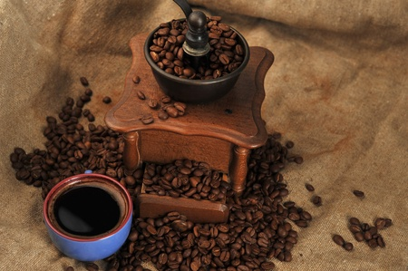 Vintage manual coffee grinder with coffee beans and cup photo