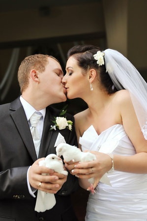 newlyweds holding white doves in their hands photo