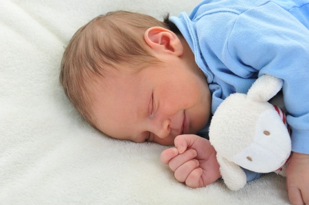 quiet baby: cute baby with toy sleeping on white blanket Stock Photo