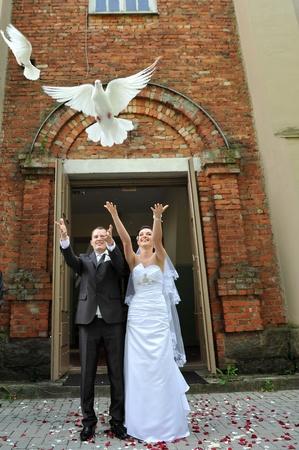 jonggehuwden het vrijgeven van witte duiven. paar op hun huwelijksdag
