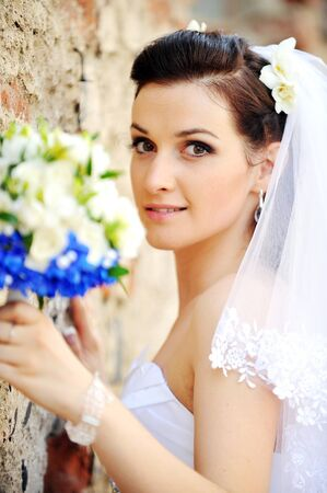 bride with flowers near an old brick wall photo