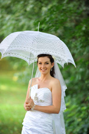 beautiful bride portrait with umbrella in park Stock Photo - 12393236