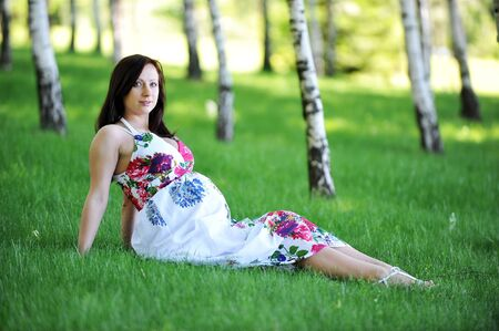 beautiful  woman  sitting on  grass in  birch grove . summers day. photo