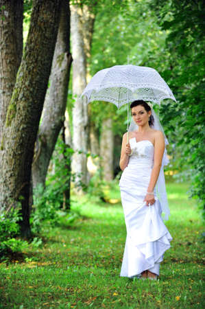 beautiful bride with umbrella walking in  park Stock Photo - 12393276