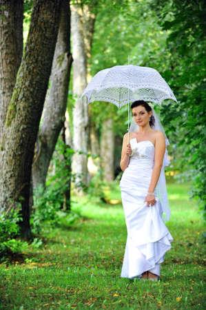 beautiful bride with umbrella walking in  park Stock Photo - 12393276