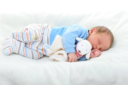 coussins: b�b� mignon avec couchage jouet sur la couverture blanche Banque d'images