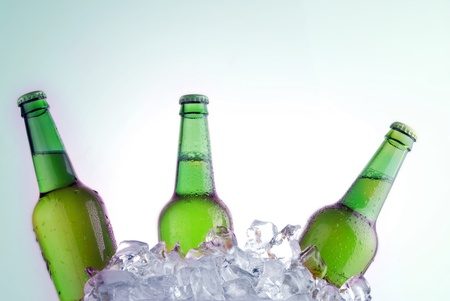 alcoholic drinks: green bottles of beer chilling on ice Stock Photo