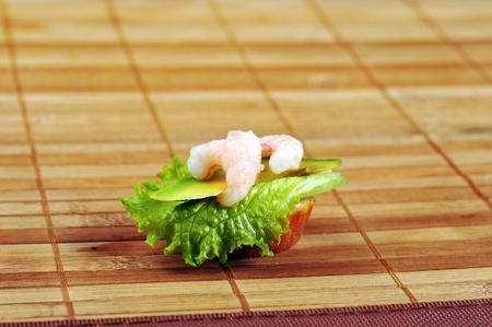 faced: Sandwich garnish with shrimps, avokado and lettuce on  bamboo napkin, snack Stock Photo