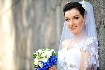 bride with flowers near an old brick wall Stock Photo - 13497340