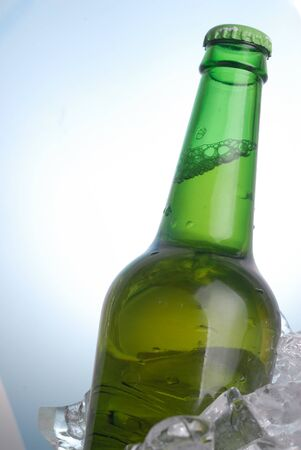 green bottle of beer chilling on ice photo