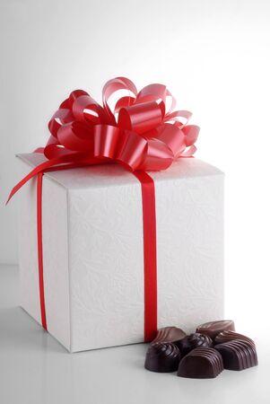 Tasty chocolates near gift box photo