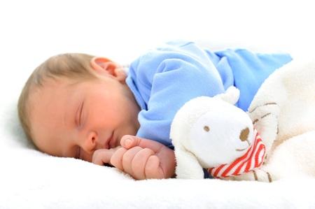 enfant qui dort: b�b� mignon avec couchage jouet sur la couverture blanche Banque d'images