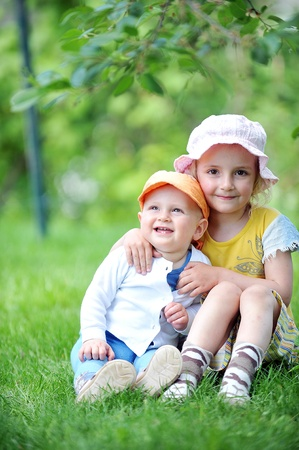 girl and her little brother sitting on  grass photo
