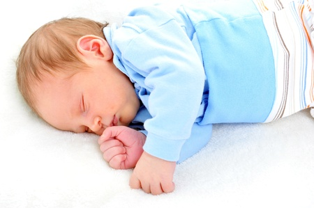 Newborn cute baby sleeping on white blanket photo
