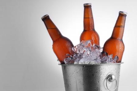 Tres botellas de cerveza de color marrón en cubo de hielo con la condensación