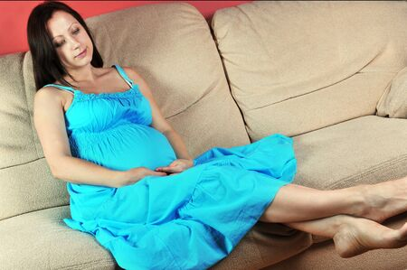 Pregnant woman  in  blue dress sitting on  couch in living room Stock Photo - 14627495