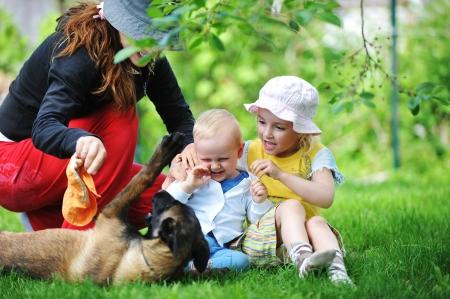 family one: ragazza e il suo fratellino che gioca con il cane su erba Archivio Fotografico