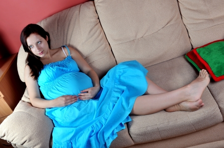 Pregnant woman  in  blue dress sitting on  couch in living room  photo