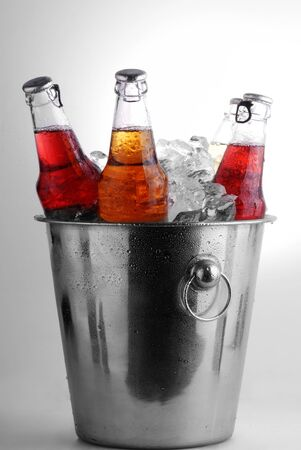 three different beer bottles in bucket of ice with condensation photo