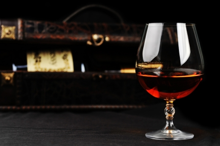 amaretto: elegant  glass of cognac and bottle in wooden case  background