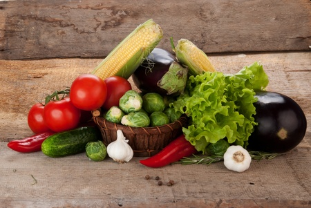Composition with vegetables in wicker basket on wooden board photo