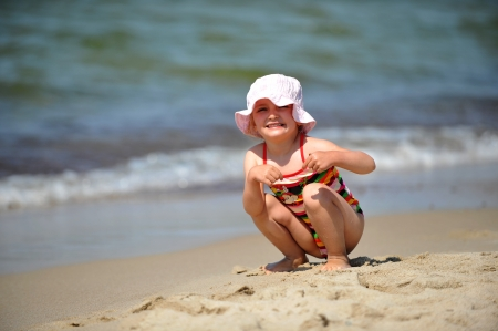Beautiful little girl in hat relaxing at beach photo