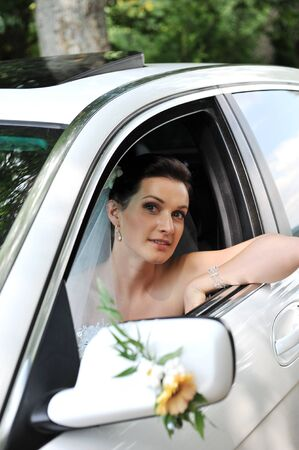 Bride with flowers in white car photo