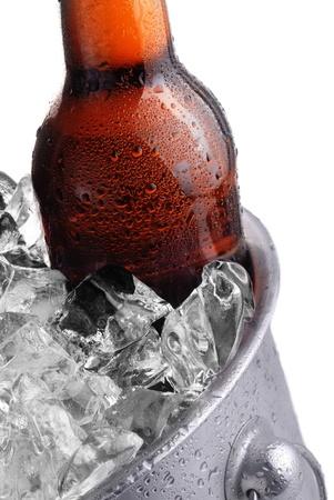 brown beer bottle in ice bucket with condensation