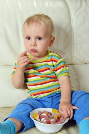 Little boy eating sweets. full bowl of candy photo