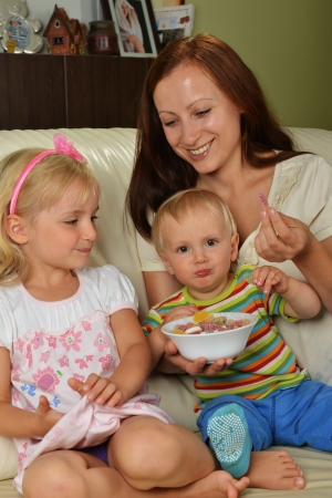 Young mother with her children at home  eating candy photo