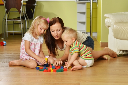 playing games: mother and her childs playing with cubes at home