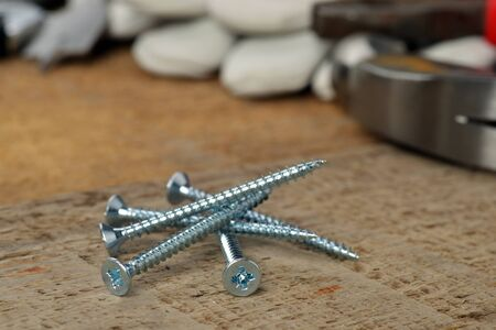 steel screws and different tools on  wooden background.  photo