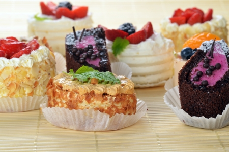 Small  cakes  with cream and  berries on bamboo table cloth  photo