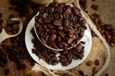 Roasted coffee beans with cup on jute hessian background Stock Photo - 15765824