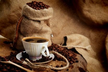 gunny bag: coffee beans in jute sack behind  cup of black coffee
