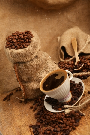 coffee beans in jute sack behind  cup of black coffee photo
