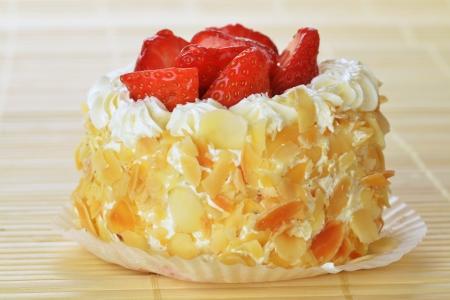 smakelijke cakes met noten en aardbeien op bamboe tafel doek Stockfoto