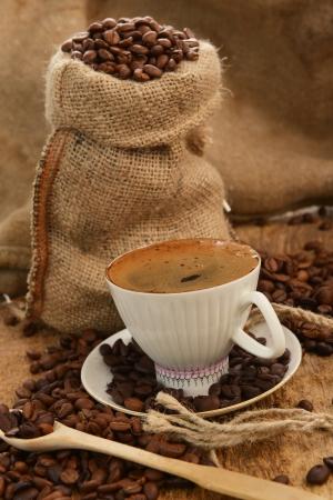 coffee beans in jute sack behind  cup of black coffee  photo