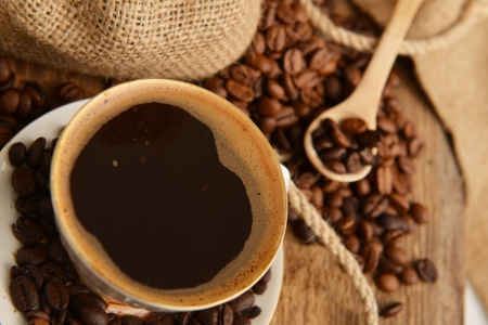 Roasted coffee beans with cup on jute hessian background Stock Photo - 15963211
