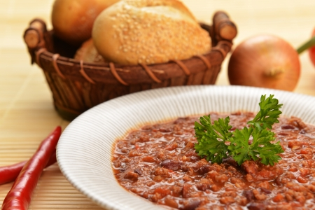 flatulence: Bowl of chili with peppers,  beans and  basket of bun