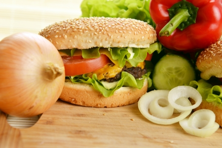 Tasty and appetizing hamburger on wooden  plate  Stock Photo