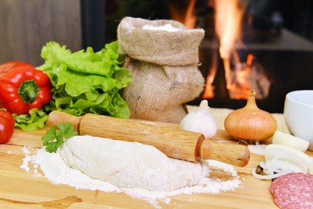 delicious pizza dough, spices and vegetables on wooden table photo