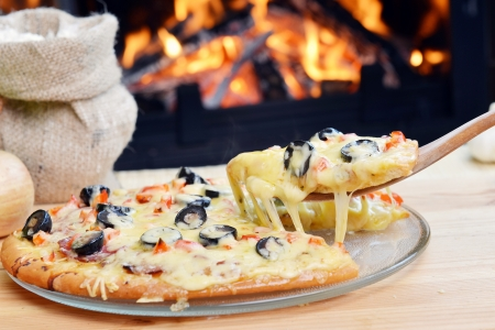 Pizza lifting slice with pepperoni and olives Stock Photo - 15962918