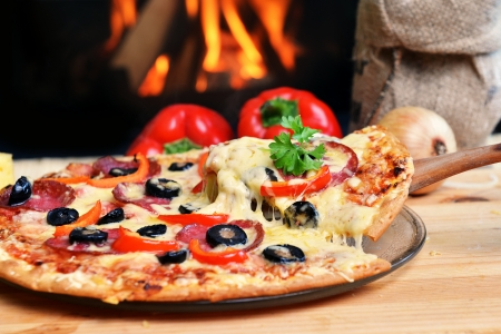 pizza: Pizza lifting slice with pepperoni and olives Stock Photo