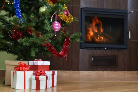 christmas eve: Christmas tree and christmas gift boxes in  interior with  fireplace