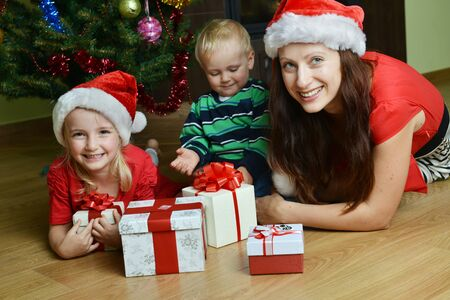 happy children with mother near Christmas tree photo