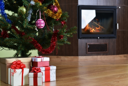 Christmas tree and christmas gift boxes in  interior with  fireplace  photo