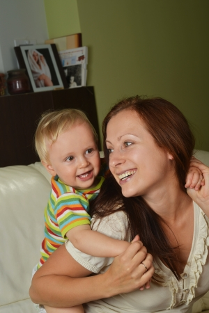 happy mother with  child at home on white sofa photo